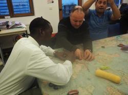 Saleh, Khalid et Wahid s'appliquent à broder un parcours de voyage sur un tissu représentant le monde.