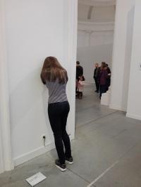 Caroline de Daniel Firman est de dos et a les avant-bras appuyés contre le mur.