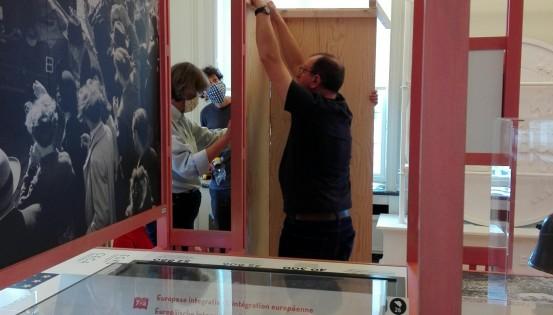 Un homme et une femme montent un panneau d'exposition dans le musée BELvue